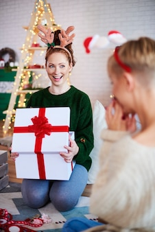 Portret podekscytowanej dziewczyny otwierającej duży, świąteczny prezent