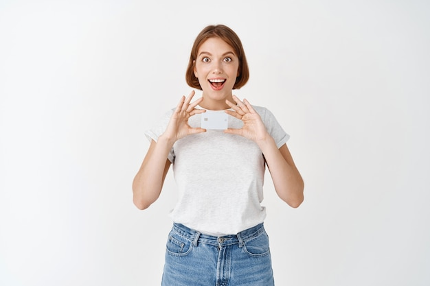 Portret podekscytowanej dziewczyny pokazującej plastikową kartę kredytową, polecam ofertę banku, stojąc przed białą ścianą