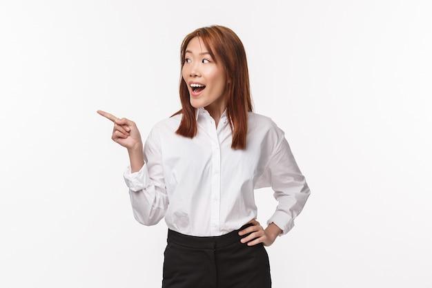 Portret podekscytowanej i rozbawionej eleganckiej młodej kobiety z azji w białej koszuli biurowej, wskazujący palec w lewo i uśmiechnięty zachwycony widząc coś interesującego,