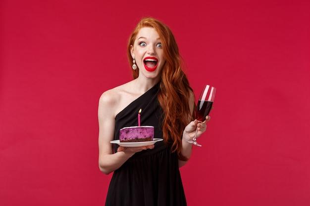 Portret podekscytowanej i rozbawionej szczęśliwej rudowłosy b-dniowej dziewczyny trzymającej tort z zapaloną świeczką i próbującej spełnić marzenie, świętujący na imprezie popijając wino, na czerwonej ścianie