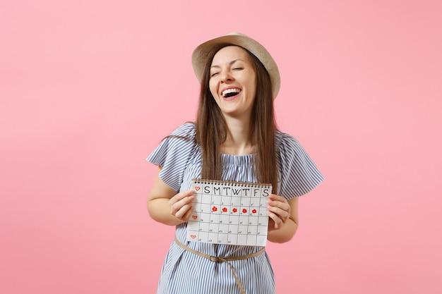 Portret podekscytowanej kobiety w niebieskiej sukience, kapelusz trzymający kalendarz okresów do sprawdzania dni miesiączki na białym tle na jasnym, trendującym różowym tle. medycyna, opieka zdrowotna, koncepcja ginekologiczna. skopiuj miejsce
