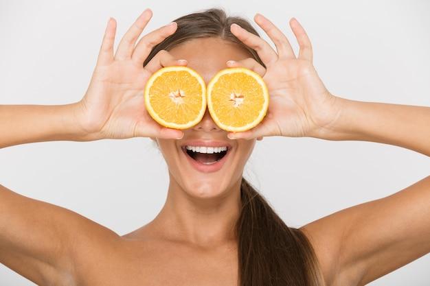 Portret podekscytowanej młodej kobiety topless na białym tle, trzymając plasterki pomarańczy na jej twarzy