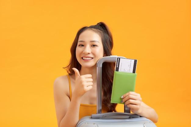 Portret podekscytowanej młodej kobiety trzymającej paszport z biletami lotniczymi z walizką odizolowaną na żółtym tle