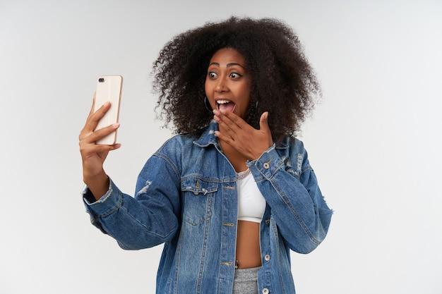 Portret podekscytowanej młodej kręconej kobiety o ciemnej skórze, która robi selfie swoim smartfonem, radośnie i zakrywając szeroko otwarte usta dłonią, odizolowana na białej ścianie