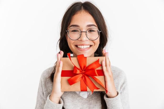 Portret podekscytowanej młodej uczennicy na białym tle nad białą ścianą trzymającą prezent w pudełku niespodzianki