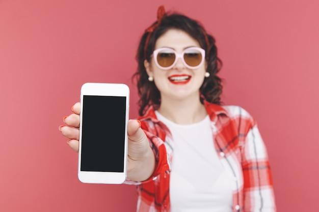 Portret podekscytowanej pięknej dziewczyny w czerwonej koszuli, trzymając telefon komórkowy na białym tle na różowym tle.