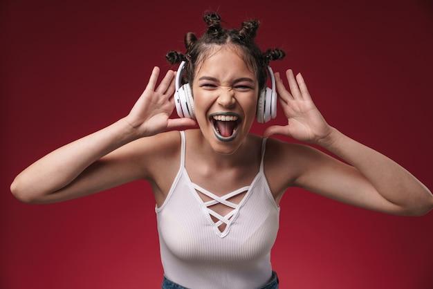 Portret podekscytowanej punkowej dziewczyny z dziwaczną fryzurą krzyczącą do kamery podczas słuchania muzyki przez słuchawki odizolowane na czerwonej ścianie