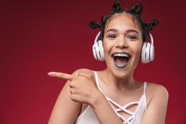 Portret podekscytowanej punkowej dziewczyny z dziwaczną fryzurą wskazującą palcem na copyspace podczas słuchania muzyki przez słuchawki izolowane nad czerwoną ścianą