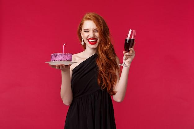 Portret podekscytowanej roześmianej wspaniałej rudowłosy kobiety bawi się na imprezie b-day, trzymając kieliszek wina i tort urodzinowy z zapaloną świecą, życząc, świętując nad czerwoną ścianą