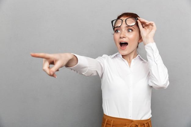 Portret podekscytowanej rudowłosej bizneswoman 20s w formalnym stroju, trzymającej okulary i patrzącej na bok w biurze izolowanym na szaro