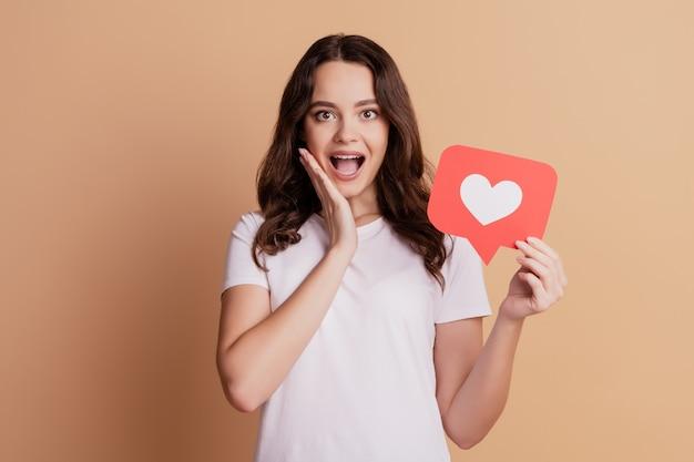 Portret podekscytowanej szalonej dziewczyny ręka policzek otwarte usta przytrzymaj ikonę serca powiadomienia na białym tle na beżowym tle