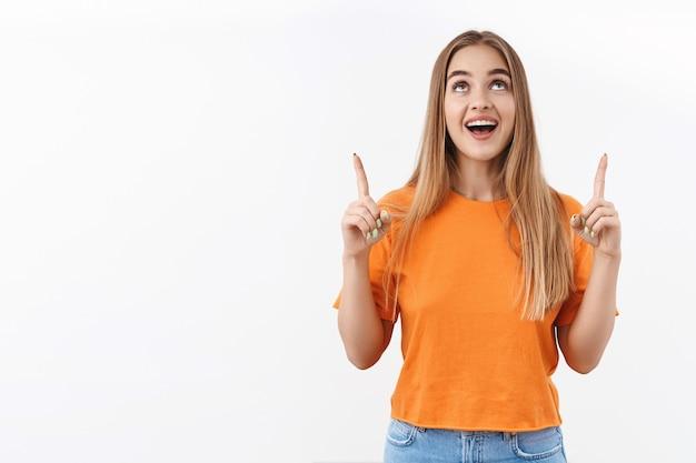 Portret podekscytowanej, szczęśliwej blond dziewczyny patrzącej i wskazującej palcem w górę na niesamowitą ofertę promocyjną, czytającej o specjalnych zniżkach, wskazującej drogę do reklamy