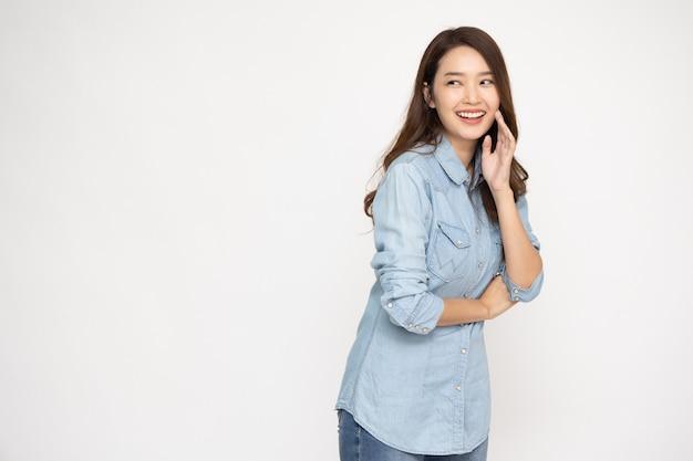 Portret podekscytowanej szczęśliwej młodej azjatyckiej kobiety noszącej dżinsową koszulę na białym tle nad białym tłem