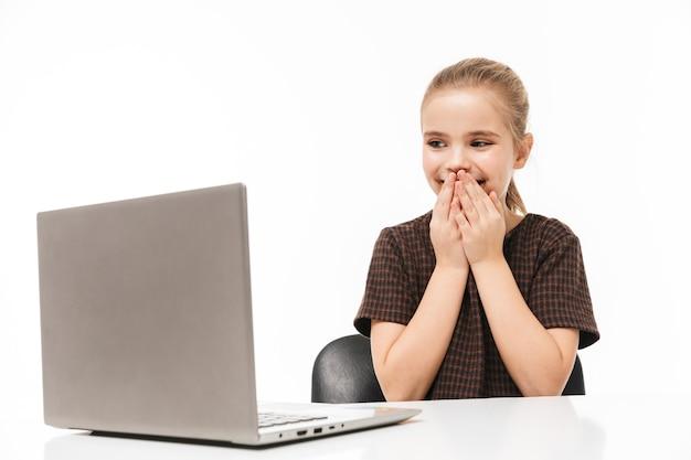 Portret podekscytowanej uczennicy cieszącej się i używającej srebrnego laptopa siedząc przy biurku w klasie odizolowanej na białej ścianie