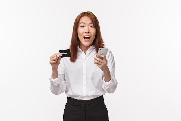 Portret podekscytowanej uroczej azjatyckiej kobiety w koszuli i spódnicy, trzymającej telefon komórkowy i kartę kredytową, składającej zamówienie przez internet, robiącej zakupy online, korzysta z depozytu bankowego, rejestruje konto w sklepie,