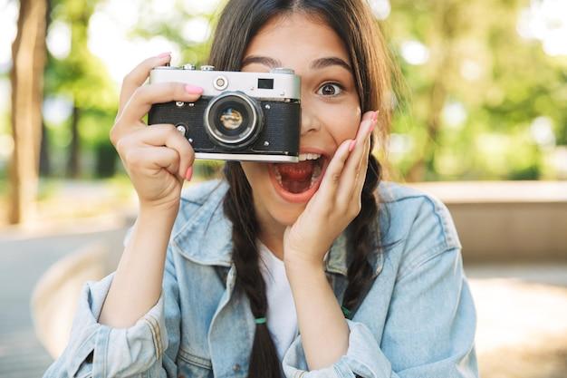 Portret podekscytowanej zszokowanej optymistycznej szczęśliwej słodkiej młodej studentki w okularach, siedzącej na ławce na zewnątrz w parku przyrody, trzymając aparat