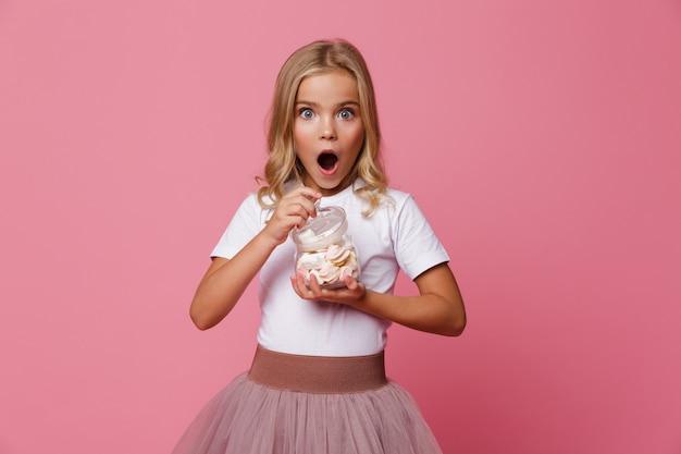 Portret podekscytowany dziewczynka gospodarstwa słoik pianki