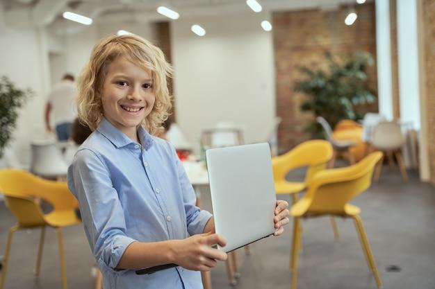 Portret podekscytowany mały chłopiec uśmiechający się do kamery, trzymając i używając laptopa stojącego w a