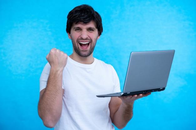 Portret podekscytowany mężczyzna posiadający komputer przenośny i świętuje sukces