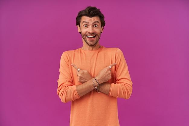 Portret podekscytowany mężczyzna z brunetką i włosiem, wskazując obie strony na miejsce