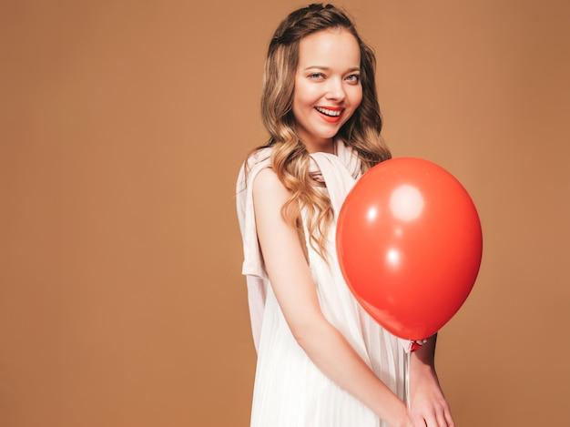 Portret podekscytowany młoda dziewczyna pozuje w modnej letniej białej sukni. uśmiechnięta kobieta z czerwony balonik pozowanie. model gotowy na imprezę