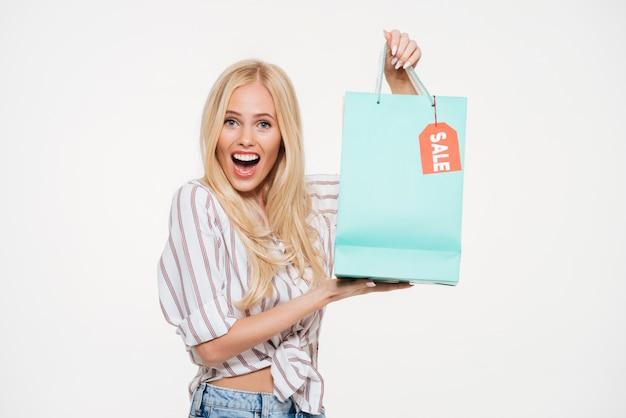 Portret podekscytowany młodej kobiety gospodarstwa torba na zakupy sprzedaż