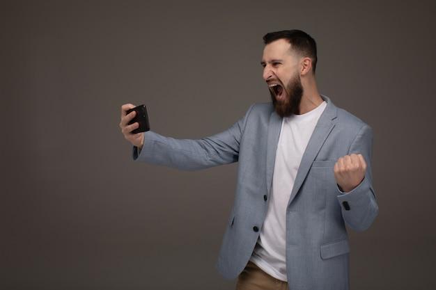 Portret podekscytowany młody brodaty mężczyzna patrząc na telefon komórkowy izolowanych na szarej ścianie, świętuje.