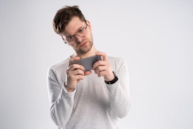 Portret podekscytowany młody człowiek w białej koszulce, grając w gry na telefon komórkowy