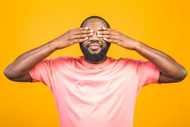 Portret podekscytowany młody mężczyzna afroamerykanów krzyczy w szoku i zdumieniu, trzymając się za ręce na głowie.