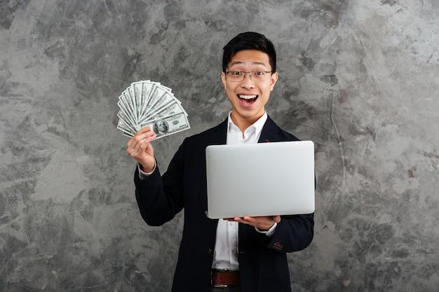 Portret podekscytowany młody mężczyzna azji ubrany w garnitur