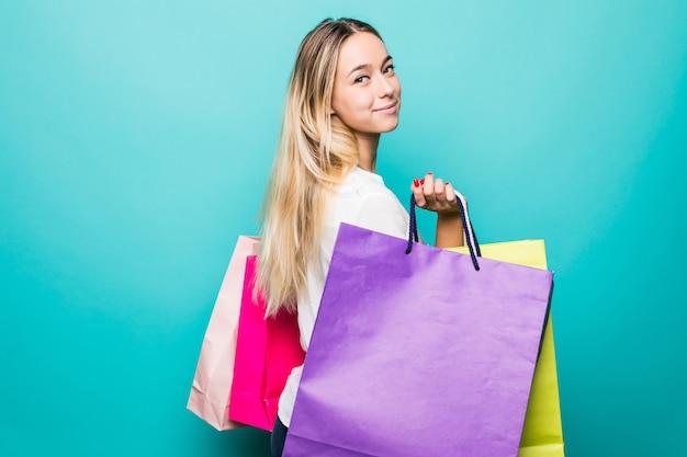 Portret podekscytowany piękna dziewczyna trzyma torby na zakupy na białym tle nad niebieską ścianą