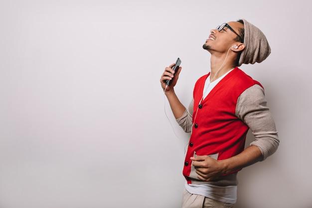Portret podekscytowany radosny mężczyzna słuchanie muzyki przez słuchawki na szaro