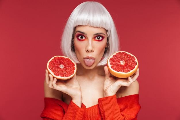 Portret podekscytowany śmieszne piękna młoda kobieta na białym tle na czerwonej ścianie gospodarstwa grejpfruta.
