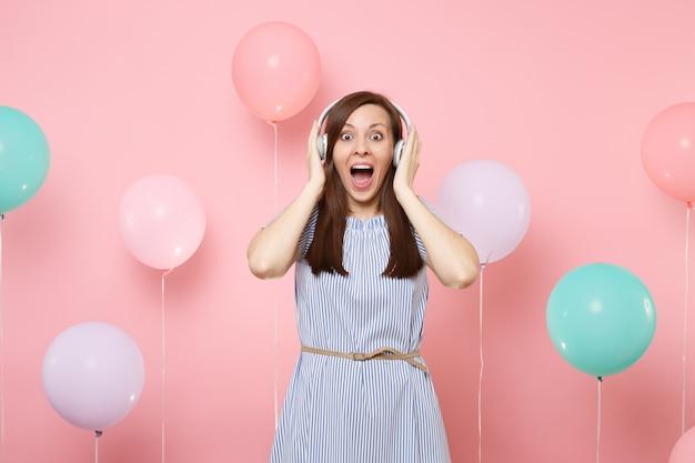 Portret podekscytowany szczęśliwy młoda kobieta ze słuchawkami na sobie niebieską sukienkę słuchania muzyki trzymając ręce w pobliżu głowy na pastelowym różowym tle z kolorowymi balonami. koncepcja strony urodziny wakacje.