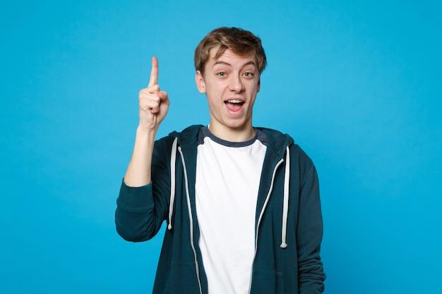 Portret podekscytowany wesoły młody człowiek w ubranie trzymaj palec wskazujący z świetnym nowym pomysłem na białym tle na niebieskiej ścianie. ludzie szczere emocje, koncepcja stylu życia.