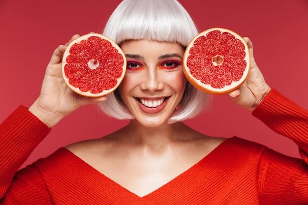 Portret podekscytowany wesoły piękna młoda kobieta na białym tle na czerwonej ścianie gospodarstwa grejpfruta.
