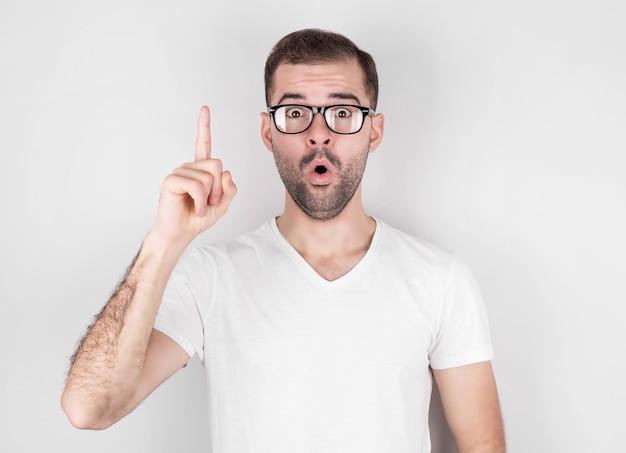 Portret podekscytowany zaskoczony mężczyzna w okularach, wskazując palcem na copyspace, na białym tle na białej ścianie