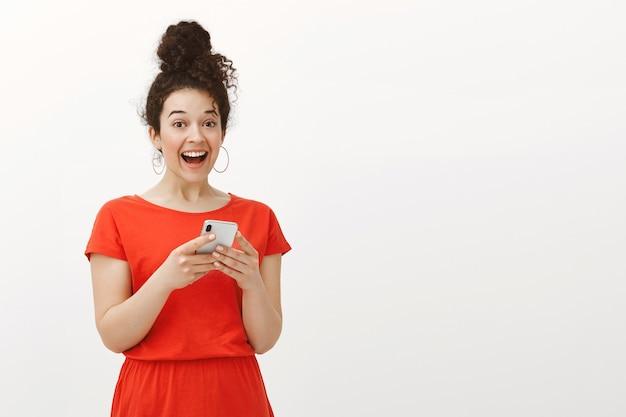 Portret podekscytowany zaskoczony szczęśliwą kobietą z kręconymi włosami w czerwonej sukience