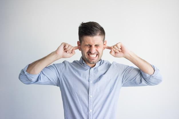 Portret podrażniony młody człowiek zatyka uszy z palcami.