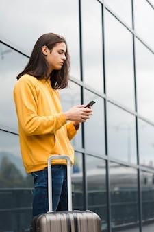 Portret podróżnik sprawdza jego telefon