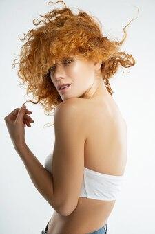 Portret pogodnej młodej kobiety z rozwianymi włosami, patrzącej przed nią
