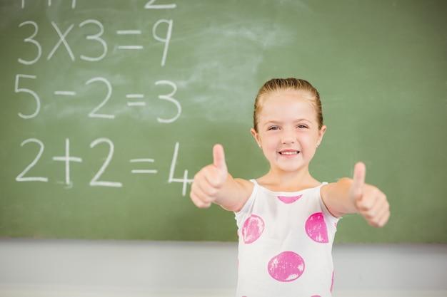 Portret pokazuje aprobaty w sala lekcyjnej uśmiechnięta uczennica