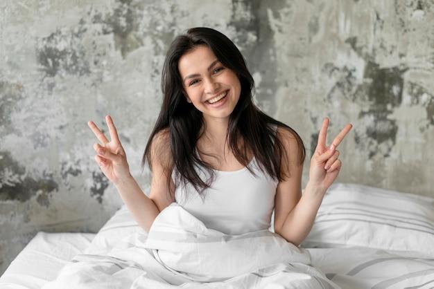 Portret pokazuje pokoju znaka młoda kobieta