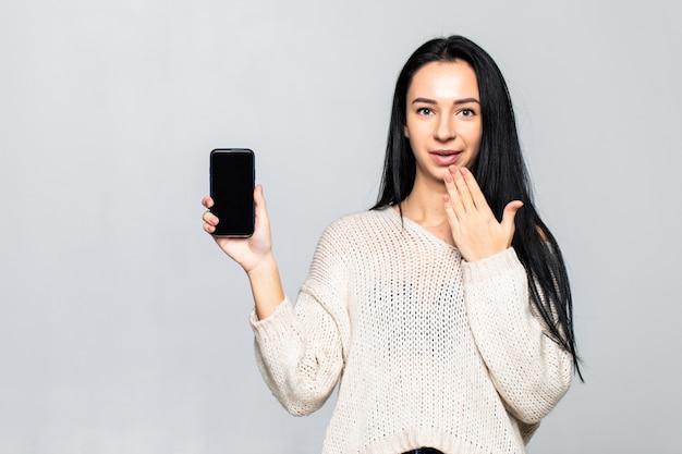 Portret pokazuje pustego sacreen telefon komórkowego kobieta podczas gdy stać odizolowywam nad szarości ścianą