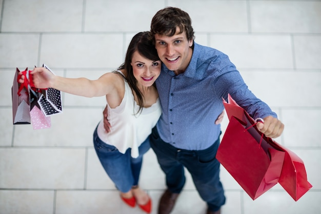 Portret pokazuje torby na zakupy uśmiechnięta para