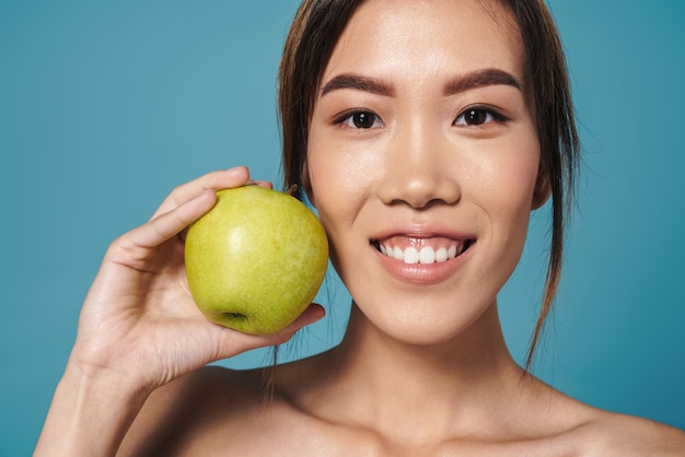 Portret półnagiej azjatyckiej kobiety trzymającej zielone jabłko i uśmiechniętej na białym tle nad niebieską ścianą