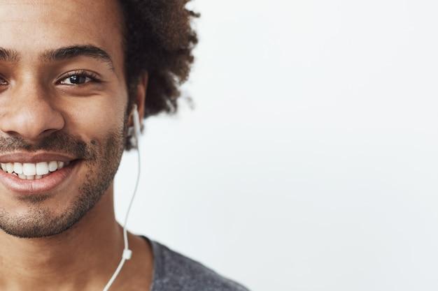 Portret połowa twarzy szczęśliwego człowieka afryka w słuchawkach uśmiecha się.