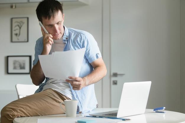Portret połowy długości mężczyzny, siedząc przy biurku z telefonem