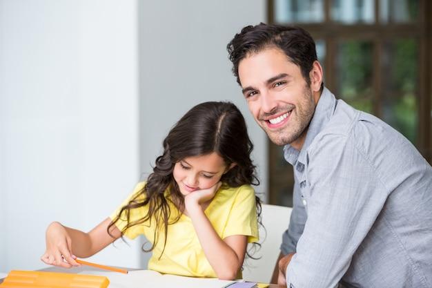 Portret pomaga córki z pracą domową uśmiechnięty ojciec