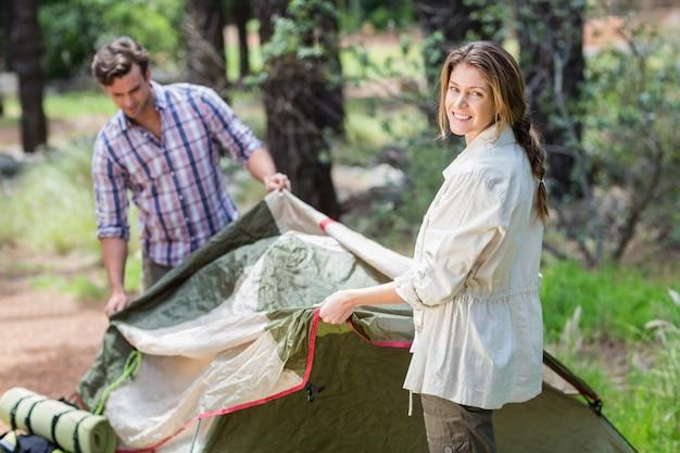Portret pomaga partnerowi w robić namiotowi kobieta